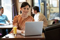Woman sitting at table in bar, using laptop computer, smiling