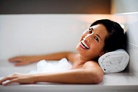 A woman lies in the bathtub as she heartily laughs at the camera