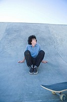 Teenage boy (13-15) sitting on halfpipe at skateboard park, looking up