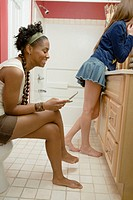 Two young women with cell phone smiling in bathroom, side view