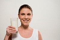 Woman holding glass of milk smiling, portrait