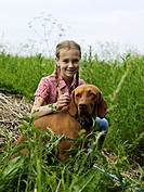 Girl (10-11) in long grass with brown dog, portrait