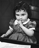 Girl (2-3) sitting at table (B&W)
