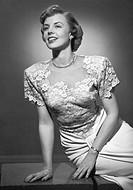 Smiling woman posing in studio, (B&W), portrait