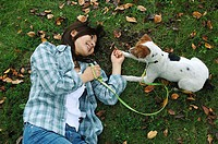 Young Asian woman playing with dog in park