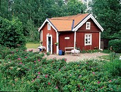 A small red summer house with plants and trees