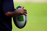 Close up of rugby ball held by player