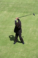 Young Asian businessman swinging golf club