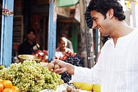 Side profile of a young man standing at a fruit stand