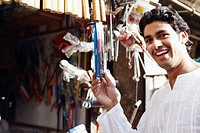 Portrait of a young man holding a packet of work tools (thumbnail)