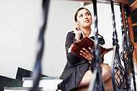 Businesswoman sitting on the staircase and holding a personal organizer
