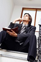 Low angle view of a businessman sitting on the staircase holding a personal organizer
