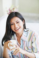Portrait of a young woman holding a mug laughing