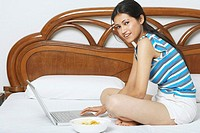 Portrait of a young woman sitting on the bed using a laptop