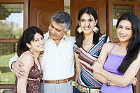 Close-up of a father standing with his three daughters