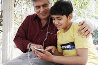 Close-up of a grandfather and his grandson looking at an MP3 player