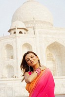Portrait of a young woman standing in front of a mausoleum, Taj Mahal, Agra, Uttar Pradesh, India
