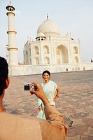 Rear view of a young man taking a photograph of a young woman in front of a mausoleum, Taj Mahal (thumbnail)