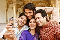 Close-up of three young men and a young woman looking at a mobile phone, Agra, Uttar Pradesh, India