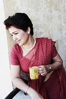Mature woman holding a tea cup looking down