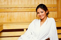 Portrait of a young woman sitting in a sauna