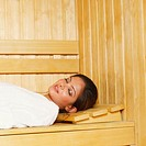 Side profile of a young woman lying in a sauna