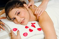 Portrait of a young woman getting a shoulder massage from a massage therapist