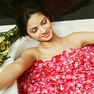 High angle view of a young woman in a bathtub full of rose petals (thumbnail)