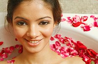 Portrait of a young woman reclining in a bathtub full of rose petals
