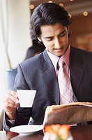 Businessman holding a cup of tea and reading a newspaper