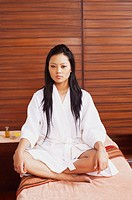 Portrait of a young woman in a bathrobe and sitting on a massage table