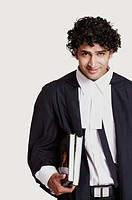 Portrait of a male lawyer holding books and smirking