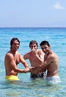 Three young men playing in the water