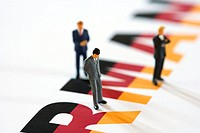 Figurines of businessmen standing on German flag