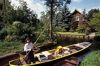 Woman rowing boat in canal, Spreewald, Lehde, Brandenburg, Germany