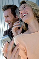 Close-up of a mid adult woman talking on a mobile phone held by a mid adult man