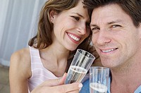 Close-up of a young couple smiling and holding champagne flutes