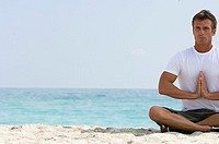 Close-up of a mid adult man sitting in the lotus position on the beach