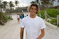 Portrait of a teenage boy holding a surfboard and smiling
