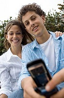 Portrait of a teenage boy and a teenage girl holding a mobile phone