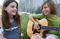 Close-up of a teenage boy playing the guitar and sitting with a teenage girl