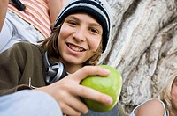Portrait of a teenage boy holding a green apple