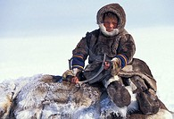 Nentsi nomad boy in traditional clothing, sitting on a stack of rendeer skins, on the tundra west of the arctic Urals, northern Russia