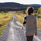Woman walking down a gravel road