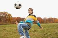 Boy bouncing soccer ball on his knee