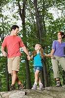 Girl and parents walking in forest