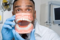 Dentist holding false teeth