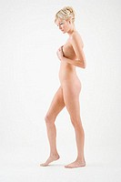 Nude woman covering her breasts