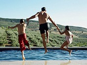 Father and children jumping into pool