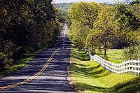 Illinois, McHenry County. Two lane country road through rolling hills, white fence alongside